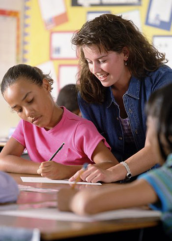 teacher working with a student one-to-one with other students nearby