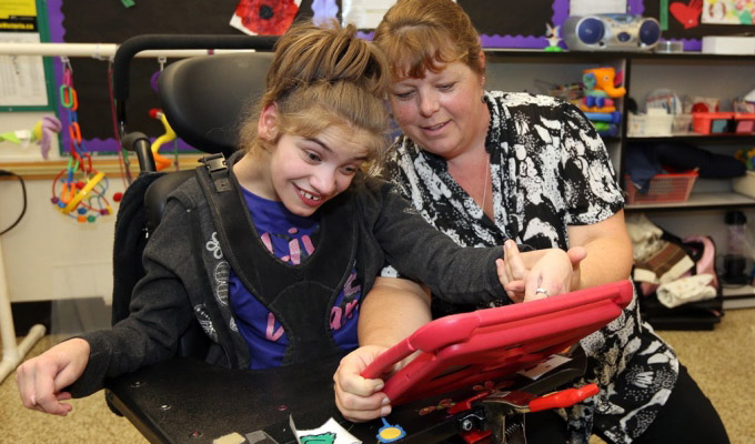 female student with physical disabilities working with assistive technology